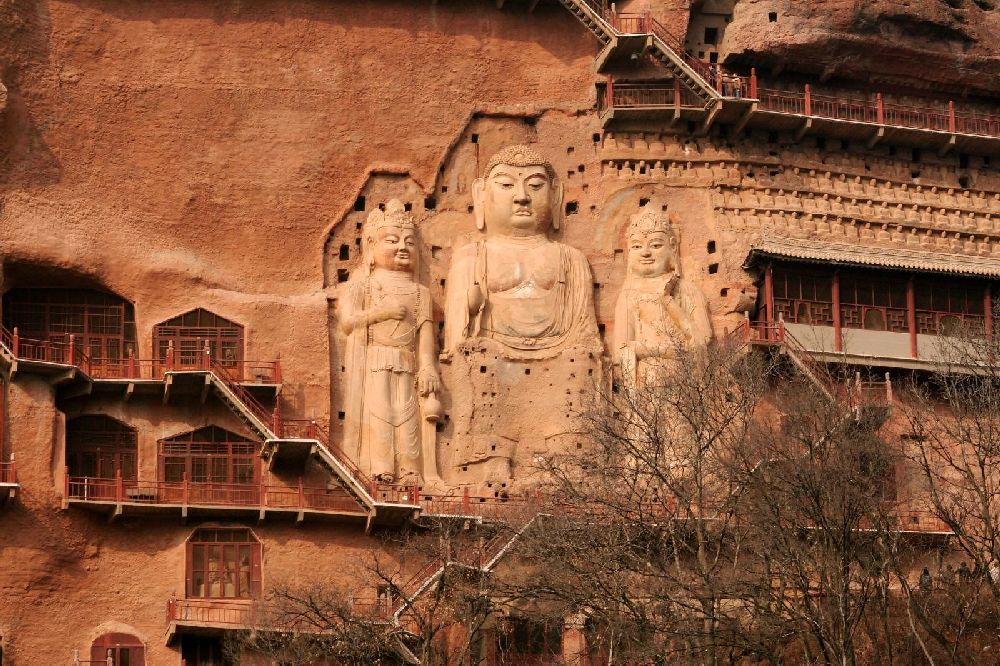 Ei Relif am Roten Sandstein, das sich über mindestens 6 Stockwerke zieht. Drei Figurn werden gzeigt. Si stehe nebeneinander. Es handelt sich um Buddhistische Figuren.