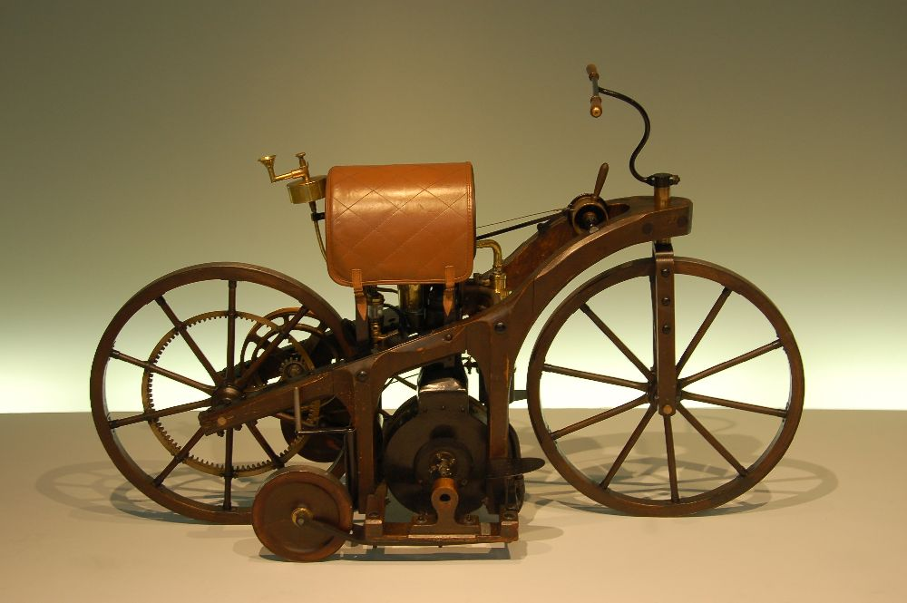 Ein vorfahr des Motororrads. Eine art Fahrrad aus Eisen das auf einr Dampfmaschine steht. Das Fahhrad hat ein art Pferdesattel als sitzt, dieser ist Braun. Es handelt sich um einen Reitwagen von Daimler.