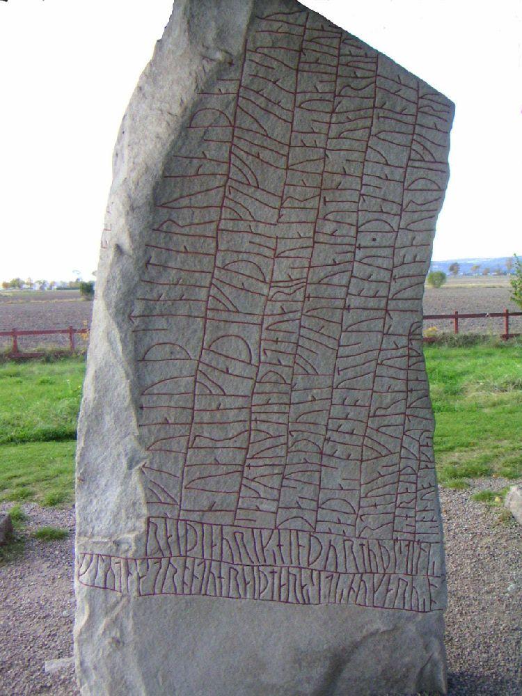 Ein Langer Großer Runenstein mit einer fein gschriebenen Langen Inschrift. Di Inschrift ist inden grauen stein eingeritzt und Rot ausgemalt. Es gibt kaum einen breich des Steines der nicht mit Zeichen überseht ist.