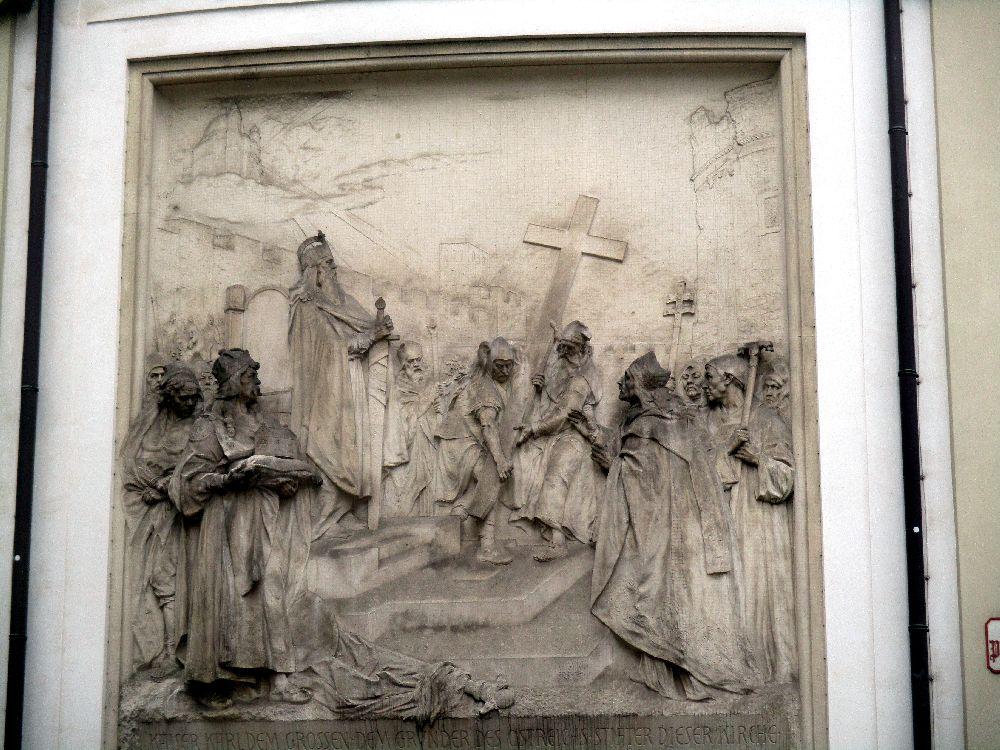 Ein Marmorrelief das eine Szene mit vielen Menschen zeigt. Karl der Große sitzt auf einem Thron während zwei männer ein großs Kreuz aufrichten.