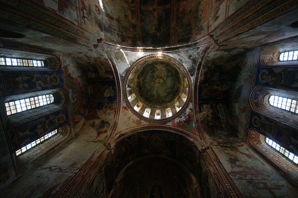Ein Dunkles hohes Kirchengebäude mit vielen nunten Malerein aus der Extremen Froschperspektive von innen fotografiert.