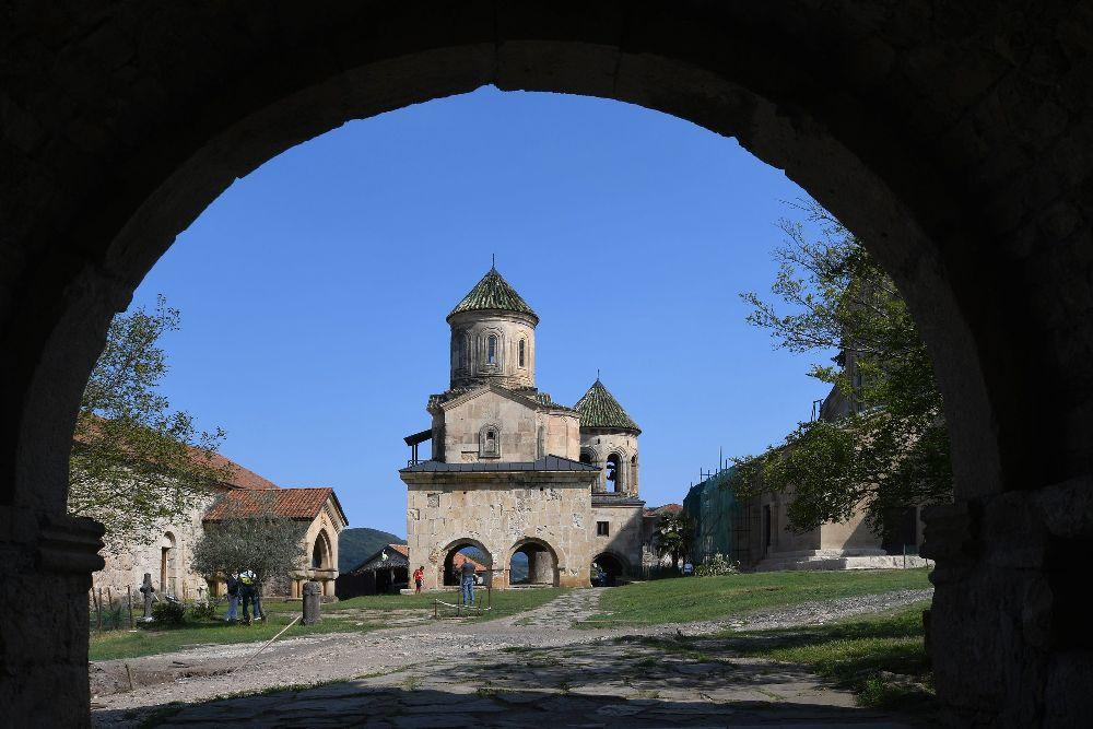 Ein Kirchenbau der auf einem Doppeltor steht. Das Gebäude ist gut drei Srockwerke Hoch bsteht aus glb-grauen Sandstein und hat einen Runden Turm mit einem spitzen Dach.