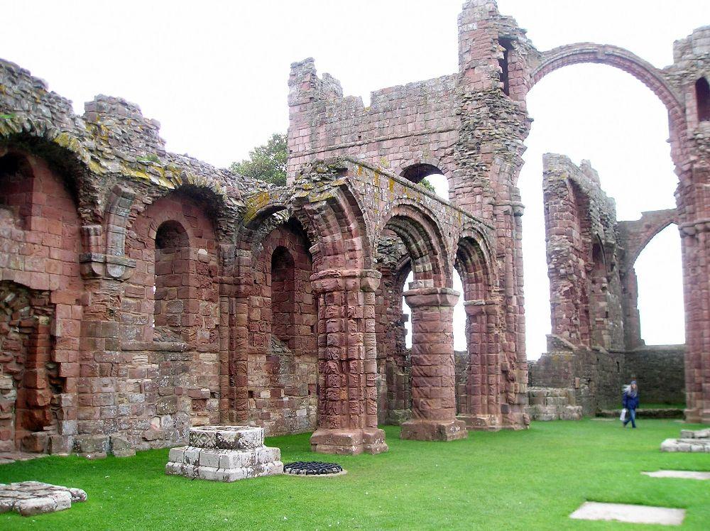 Ruine aus rotem Stei auf grüer Wiese. Es ist das Kloster Lindesfarne in Ostengland. Zu sehen sind ein paar Bögen eines Gangs.