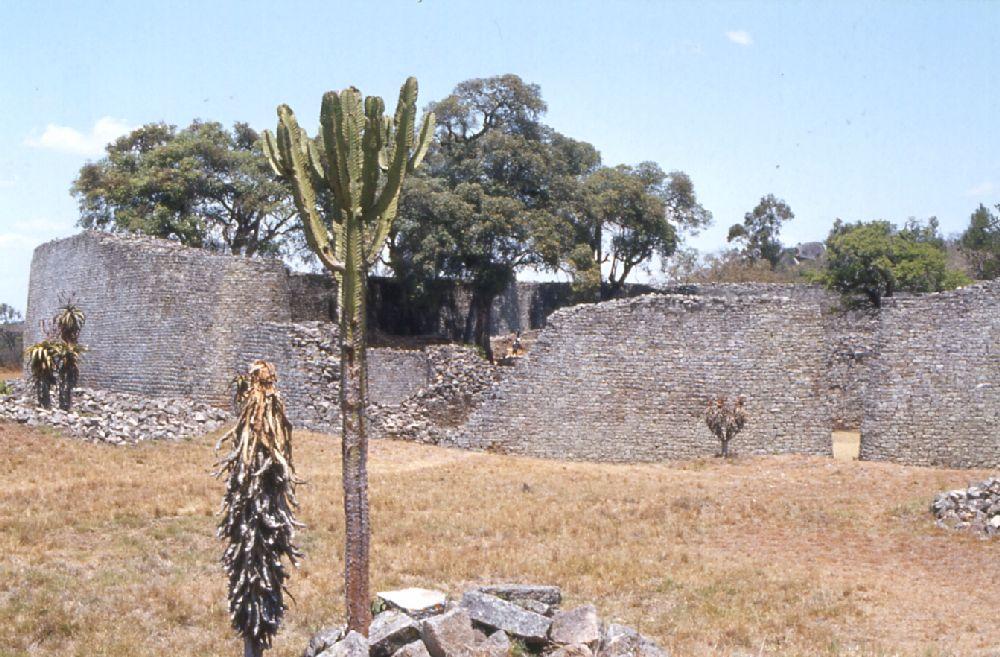 Eine hohe, rund verlaufende Mauer in der Steppe. Die mauer ist teils eingestürzt-