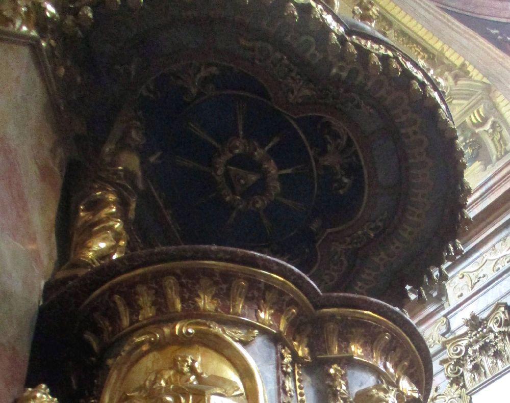Das Auge in einem Dreiek umgeben von einer Elpise mit Strahlen. Das goldornamet ist vor einm Blauen Grund, es zeigt das Allsehed Auge Gottes.