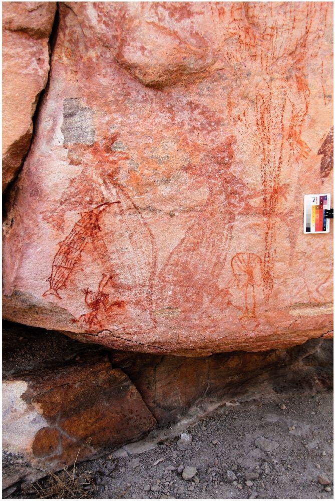 Dunklrote plastisch Ritzungn auf im hllrrote Fels. Mehrere Figuren aus roten plastischen strichn sind zu sehen. Teilweise sind sie sehr verblasst.