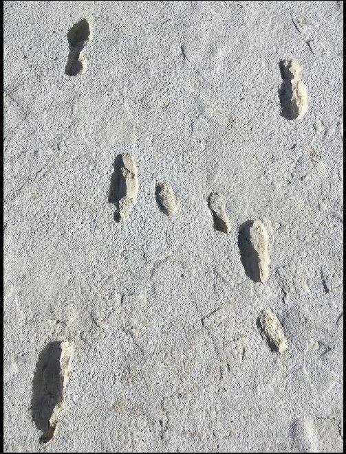 Fusspuren im weisen Sand. Deutlich zu sehen, sie stammen von Kind und Erwachsenen.