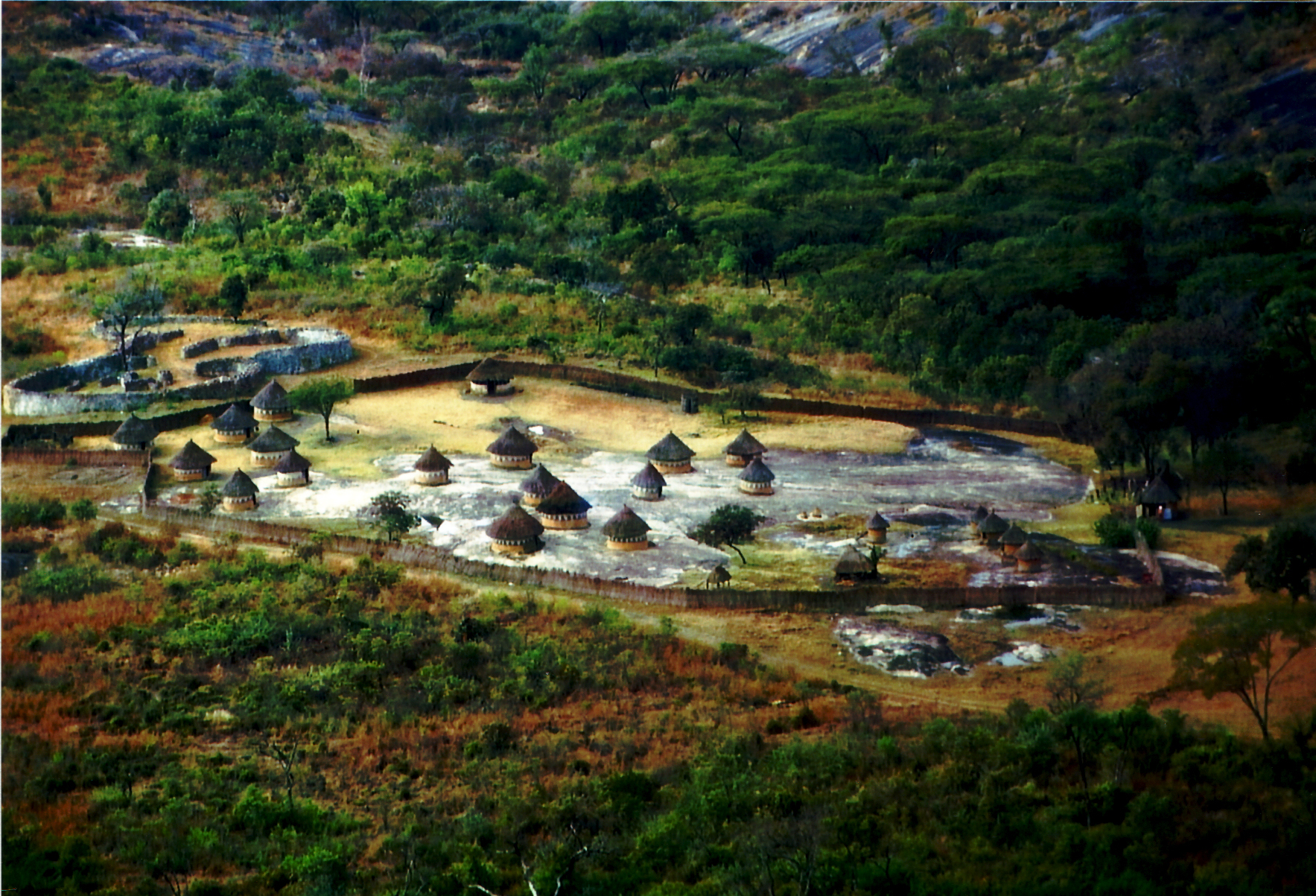 Grafik eines große mit einer Pallisade umgebenen Dorfes mit runden lehmhäusern.