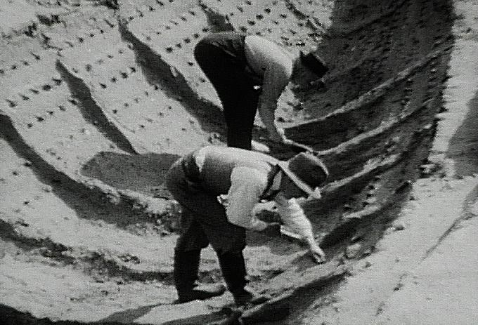 Zwei Männer mit Hut in einem Holzboot. Sie graben es gerade aus. Schwarz Weiß bild aus Sutto Hoo