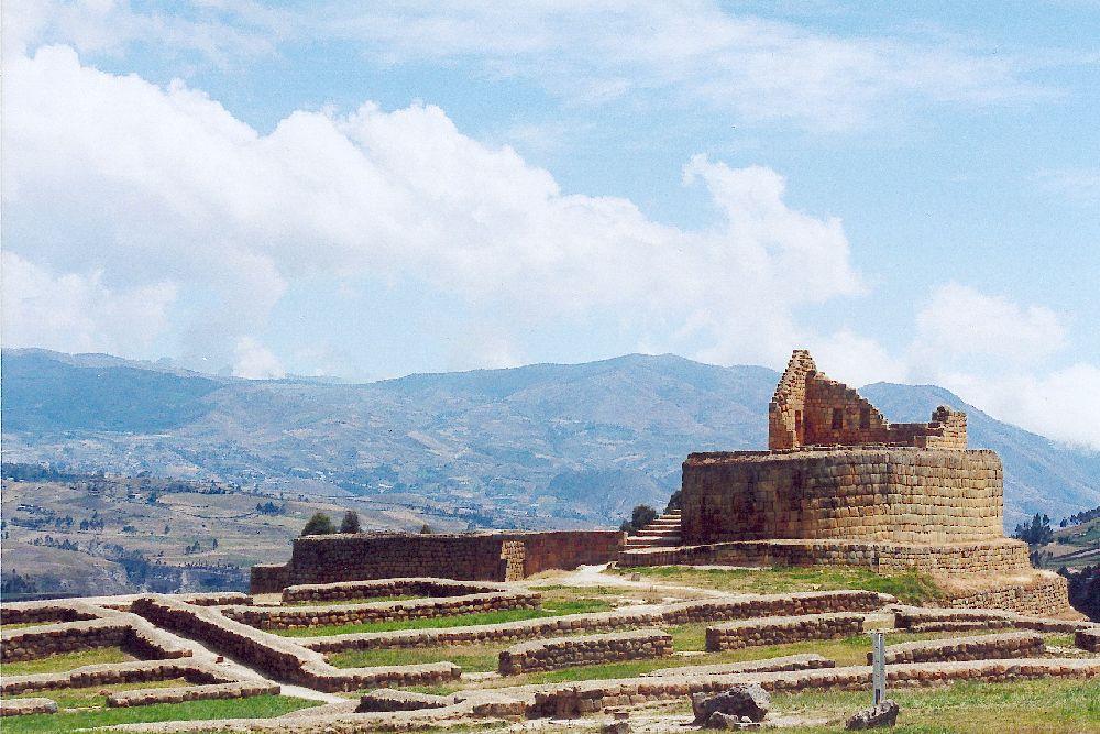 Die Ruienen von Ingapirca. Kniehohe mauern ziehen sich über einen Bergsporn, an der höchstn stelle steht ein rst eines kreisrunden Gebäudes.
