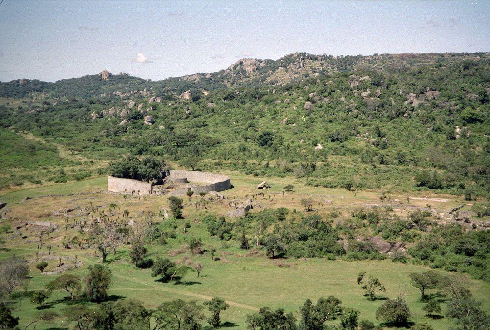 Eine grüne Ebene im Hintergrund Berge. Auf der Ebene stehen graue Ruienen. Eine Kreisförmige Mauer.