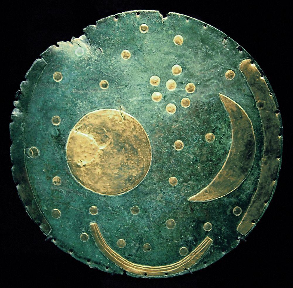Eine Runde Scheibe aus Kupfer mit 32 goldenen Punkten, es handlt sich um Strne. Dazu gibt es einen großen Goldfleck, villeicht eine Sonne daneben ist eine Goldene Sichel, vieleicht ein Mond, ud dadrunter ist ine Weitere Sichel, vielleicht ein schiff.
