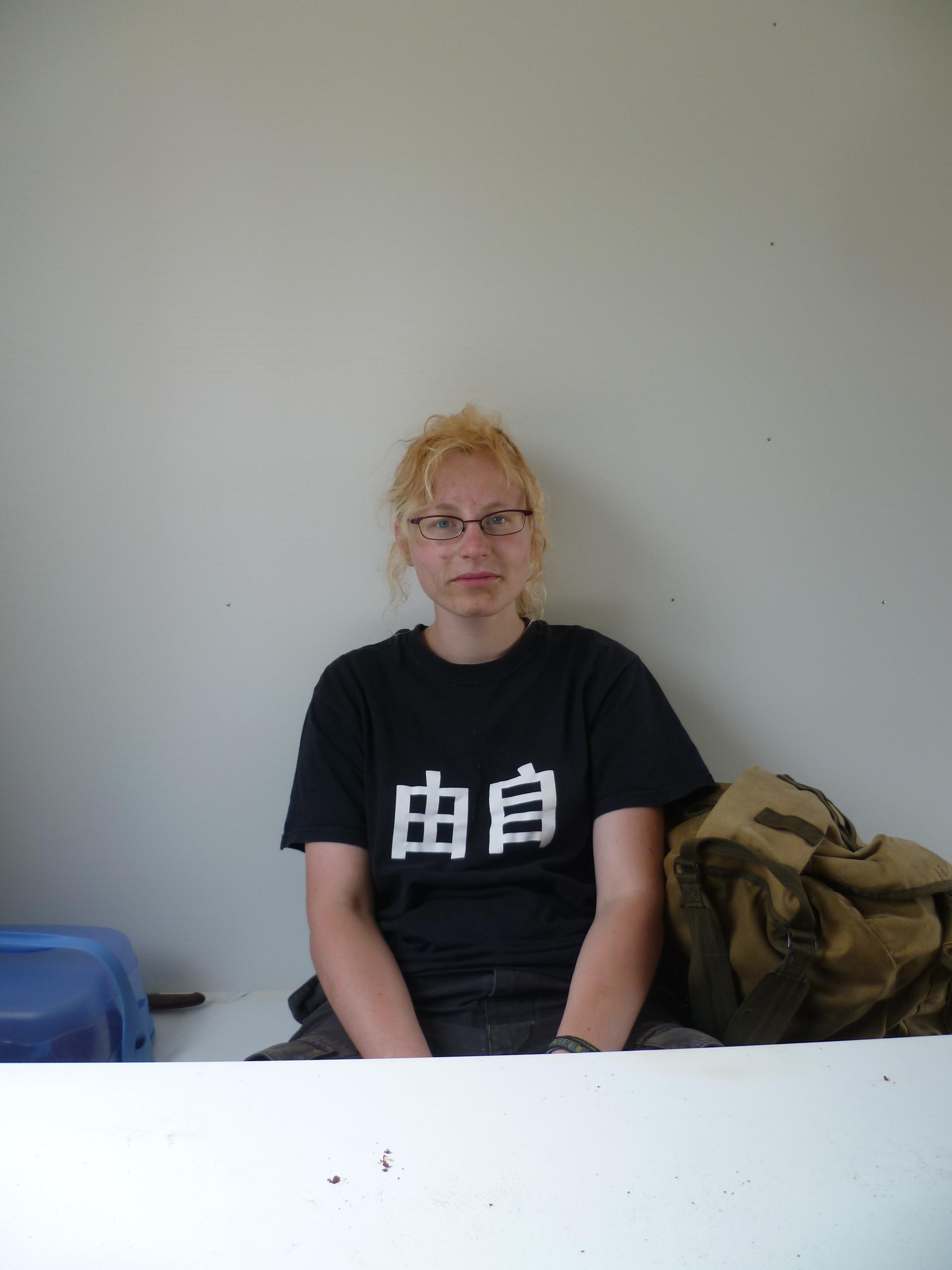 Eine Frau mit dreckiegem Gesicht sitzt und guckt Müde in die Kamera.