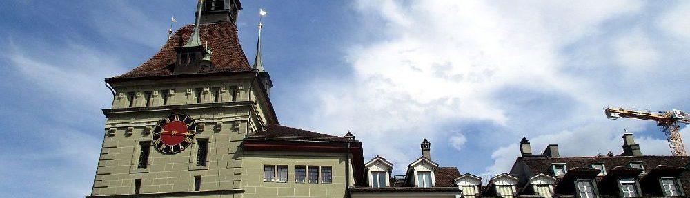 Eine eng aneinandergebaute Häuserreihe.Auf der Linken Seite ist ein Turmangebaut.