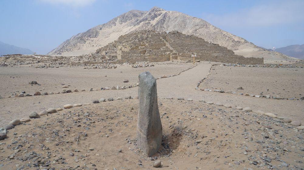 Im Vordergrund ist eine Große Steinsäule zu sehen, und im hintergrund führt ein mein Steinen begrenzter Weg zu einer Pyramide.