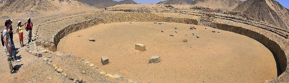 Eine runde massive Baustruktur hebt sich vom Wüstenboden ab. Es handelt sich um eine mehrere meter dicke mauer, die etwa 1 meter hoch ist.