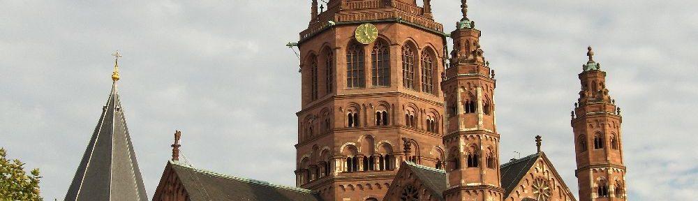 Mainzer Dom aus rotem Stein. Der Sakralbau hat einen großen Zentralen Turm mit einem spitzen Dach