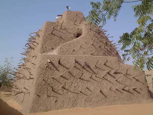 Eine Pyramide aus Lehm. Aus dem Bau ragen überall Hälzer hervor. Die Pyramide ist in drei Stufen gebaut.