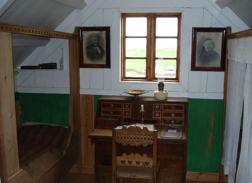 Ein Holzvertäfelter zpitz zulaufender Raum. Untern Grün gestrichen oben weiß gestrichen. Links und rechts steht ein bett, in der mitte ein Schreibtisch an einem Fenster.