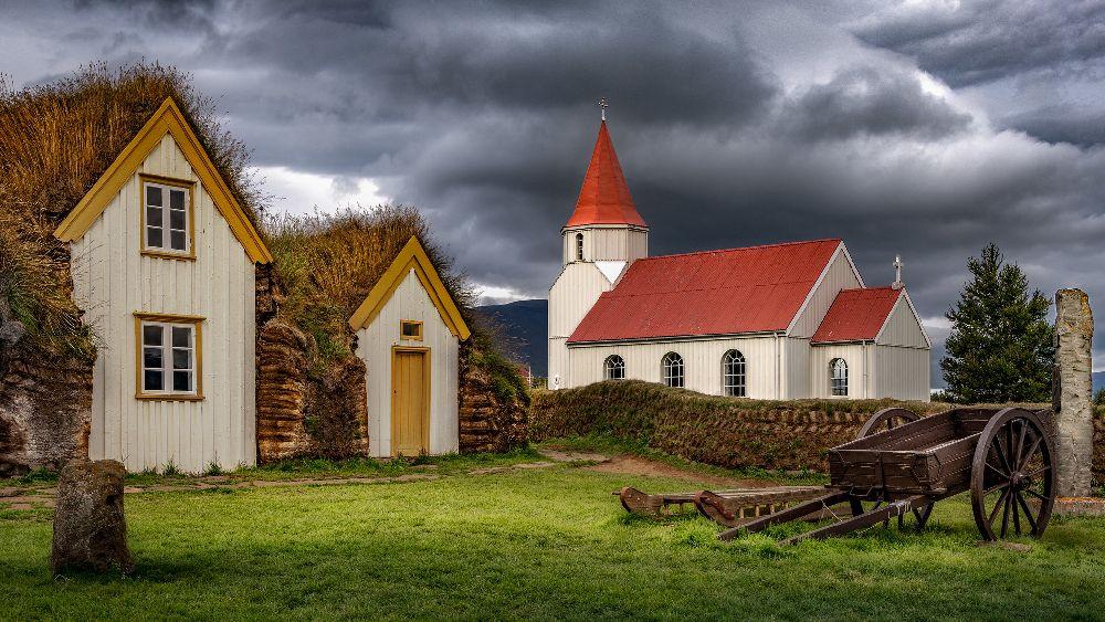 Die Kriche von Glaumbaer, sie besteht aus weißem Holz und hat ein rotes Dach. Danaben stehen die Grasßbauten aus dem 19. Jahrhundert.