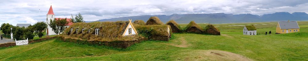 Gebäude aus Gras die dicht aneiander gebaut sind. sie stehen in einer art halbkreiscluster zueinander.