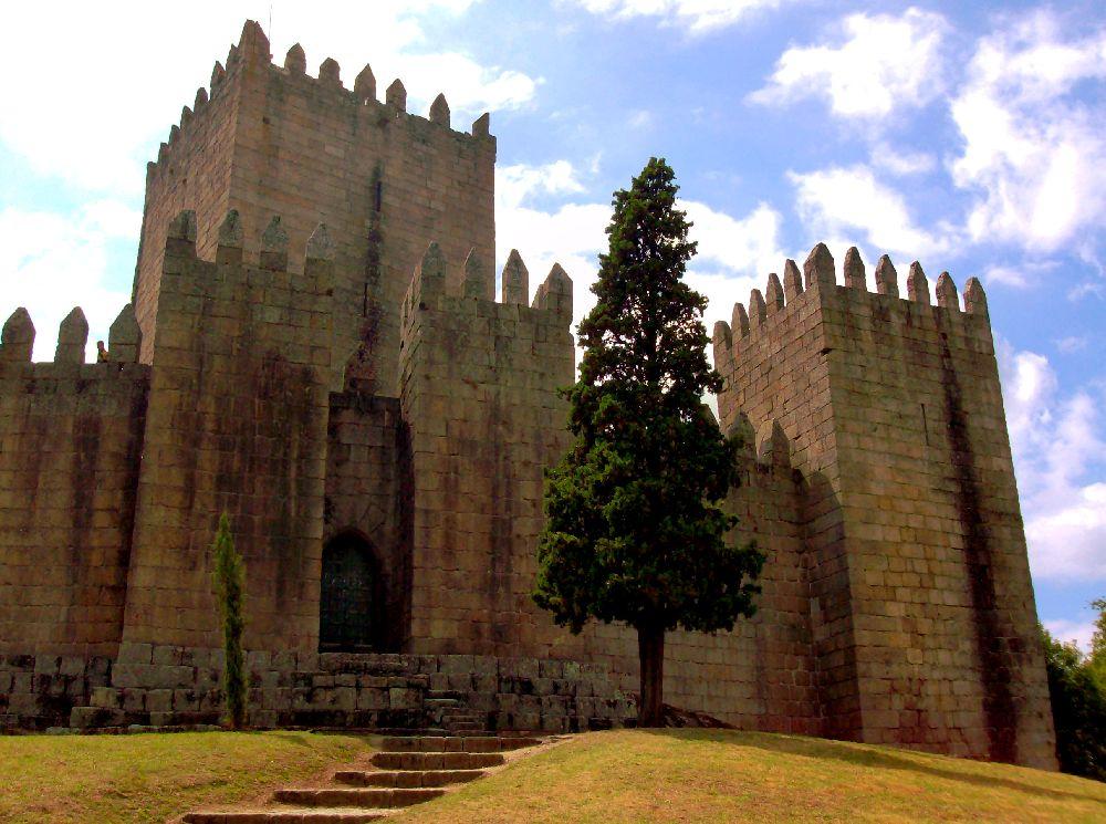 Eine Burg aus Rotbraunem Stein auf einer Gelben Wiese. Die Burg hat riesiege Zinnen und Massive Türme.