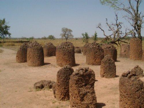 Ein Savannenfeld das vollgestellt ist mit Monolithen. Diese sind Rund, und oben auf ihnen draus liegen viele kleine aufeinandergestapelte Steine.