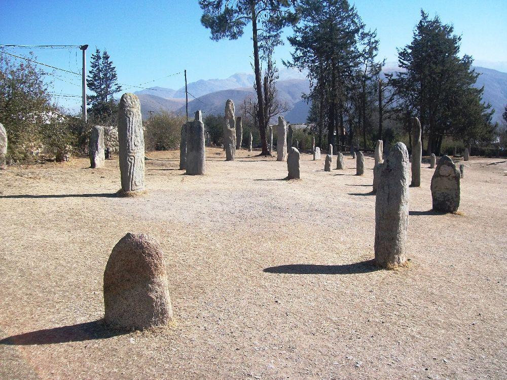 Der Hunacapark in Argentinien. mindesten 15 Hunaca sind im Vordergrund zu sehen, nach hinten hin sind es noch mehr. Die Megalithen sind verschieden groß und stehen auf trockenen Erdboden.