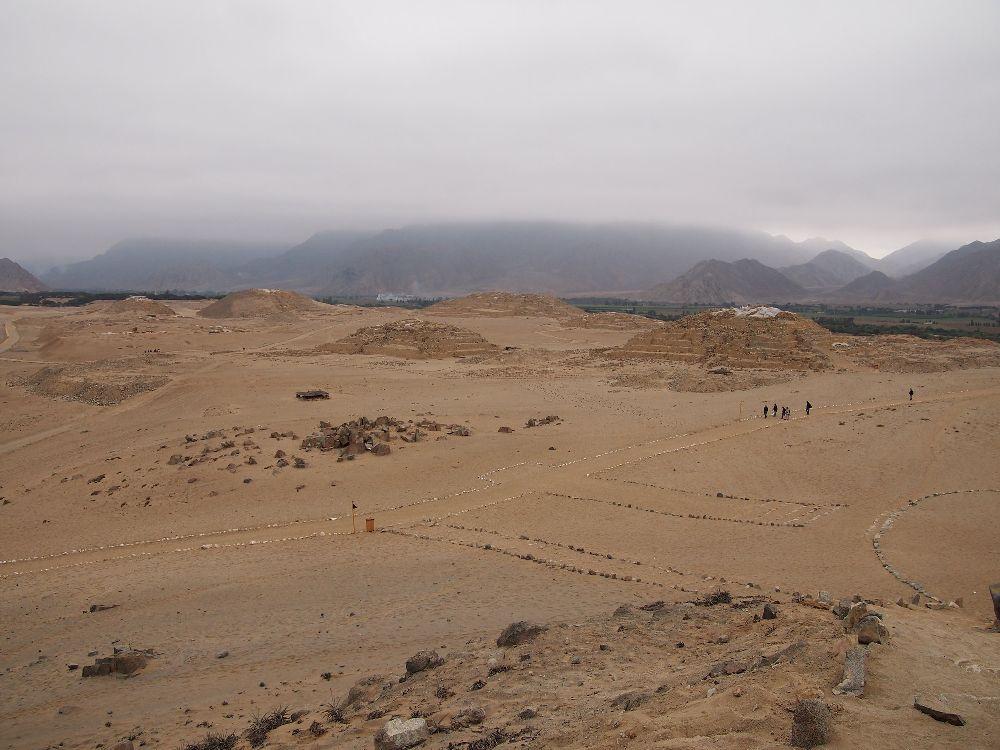 Im Hintergrund verschwinden die Anden in den Wolken. Im Forderung dind die Ruinen von Caral zu sehen. Eine Strasse führt in Richtung von Pyramieden, davorgelagert ist ein bereich mit vielen kleinen Gebäuden und eine Prachtstrasse führt aus dem Bild heraus.