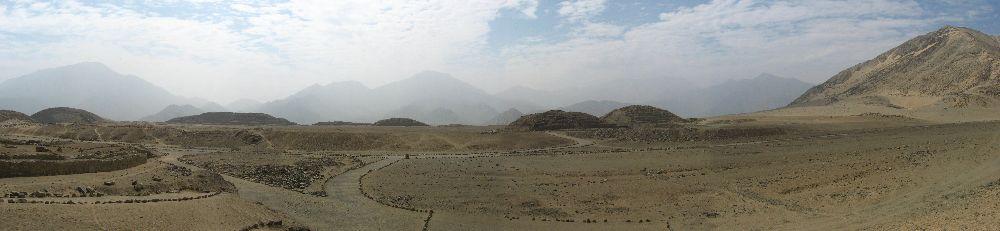 Im Hintergrund sind Braune Große Sanddünen und Berge zu sehen, im Vordergrund die Flache Grüne Landschaft in der sich die Ruienen von Caral erstrecken.