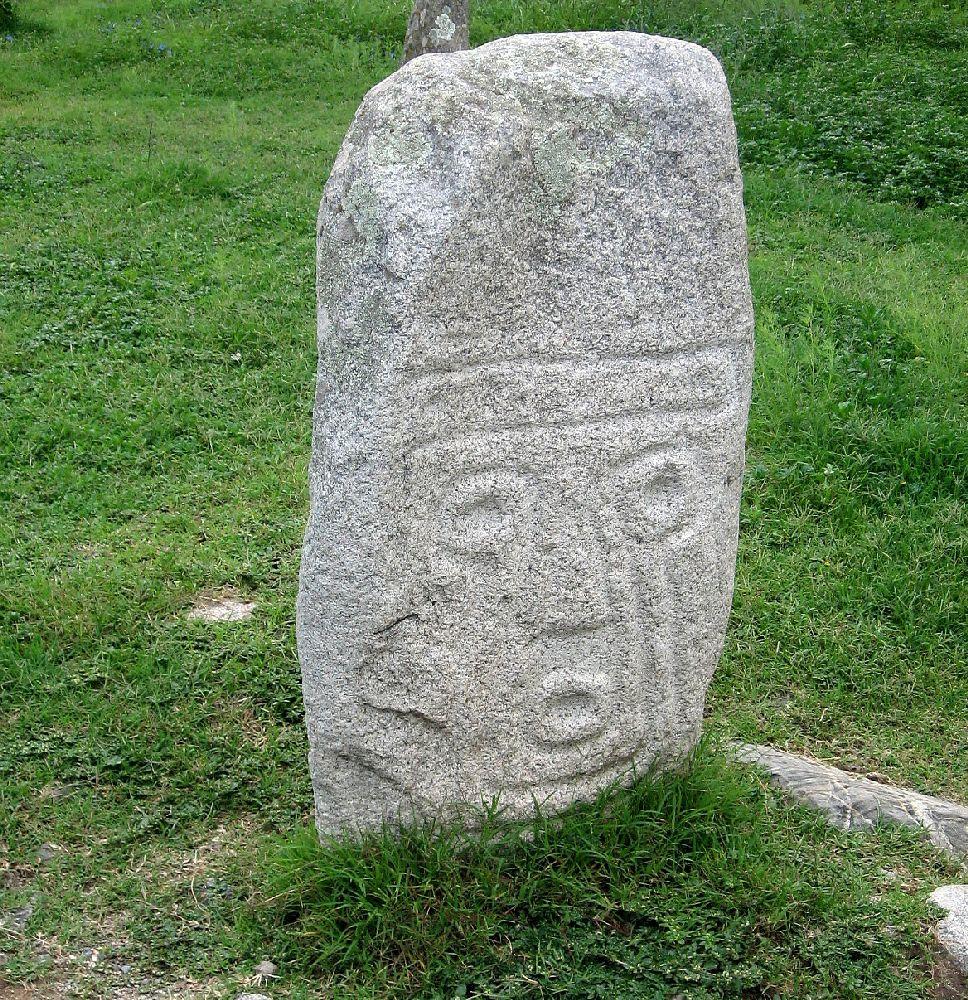 Ein Megalith mit einem Gesicht. Augen und mund sind durch Kreise dargestellt. Nase und Kinn durch Linien
