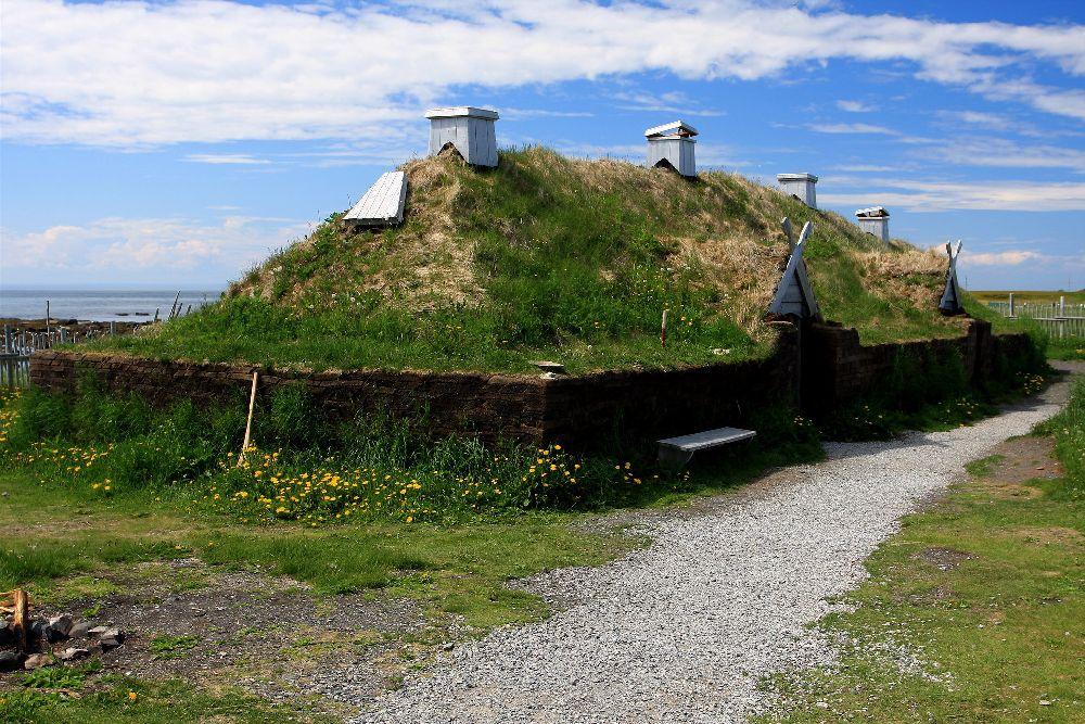 Ein Haus aus L´Angse aux Medows. Es handelt sich um einen Holzbau der rundum mit Gras bewachsen ist. Alles ist sehr Grün. Löwenzah Blüht an dem Haus und der Himmel ist Blau.