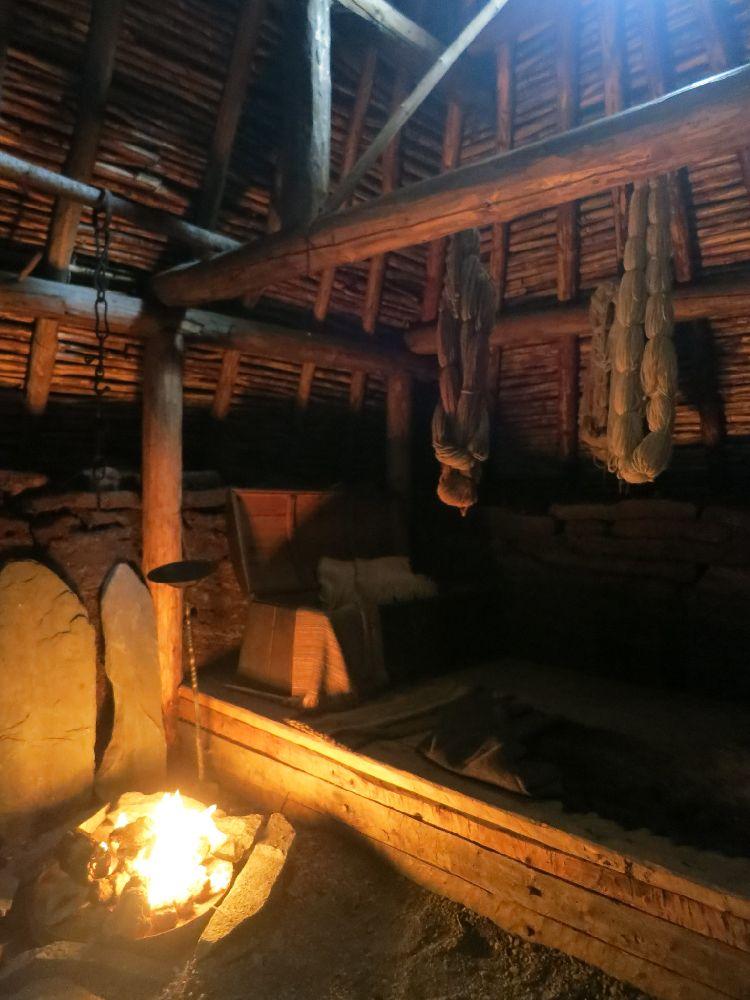 Innenraum eines Grassodenhauses. Eine Feurstelle erhalt den Dunklen Raum der Ganz aus Holz besteht. Er ist gemütlich eingerichtet mit einem Sessel und einer Kiste.