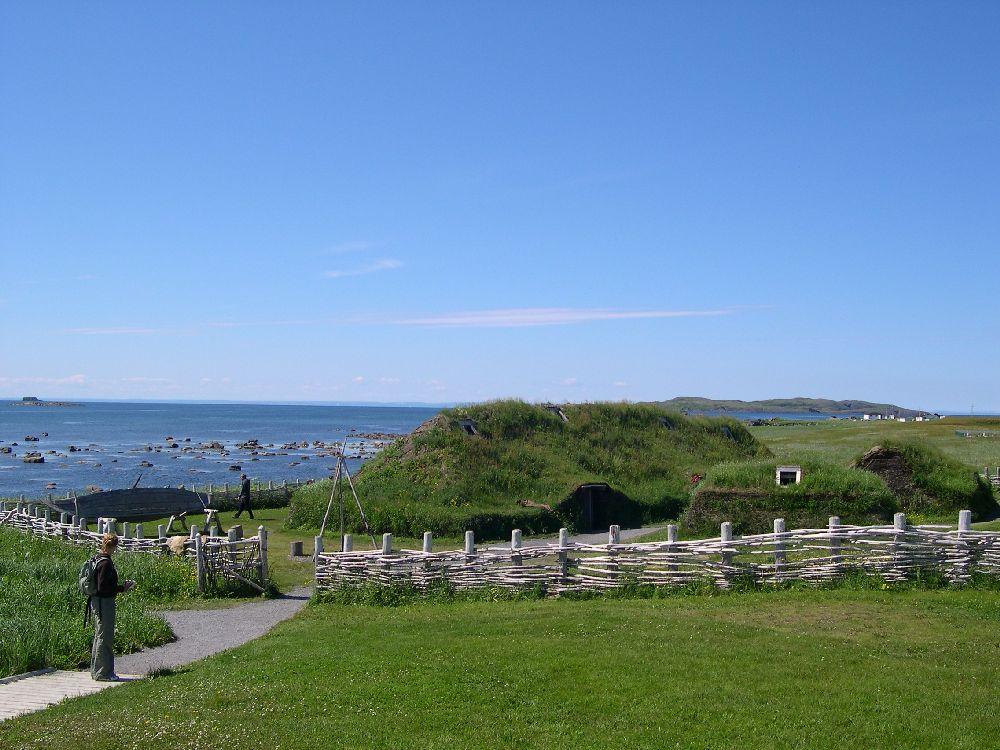 Die Grassodenhäuser aus Neufundland von weitem. Sie sind so Grün wie der Boden. Eine Pallisade aus geäst umgibt die Siedlung, im Hintergrund ist das Meer zu sehen.