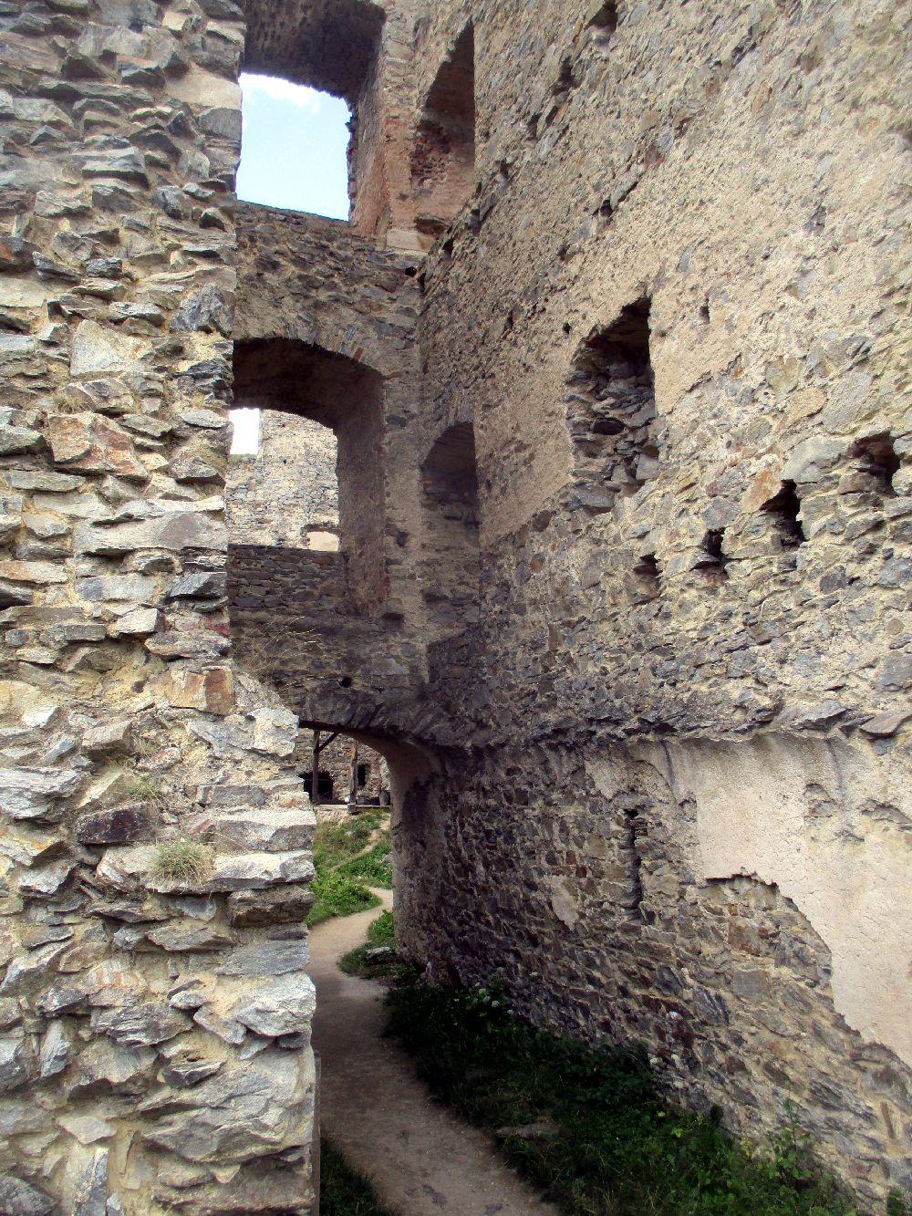Ein massiever Mauerzung mit vielen Bogenförmigen Fenstern. Es handelt sich um teils zusammengefallene Begäude von denen nur graue Steinmauern übgirg sind. Doch es ist deutlisch zu sehen, das das Gebäude einmal sehr groß war. 3 Stockwerke sind anhand der FFensterlöcher zu sehen.