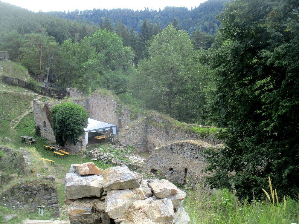 Ein Foto mit der Aussicht von der Höchsten erdgesossstelle von Burg Maisstein. Es ist deutlich zu sehen das die Burg auf einem Sehr steilen Plateau gebaut wurde. An einer tieferenstelle sind Ruinen eines Burgnebengebäudes aus grauen Steinmauern zu sehen. In den Ruienen stehlt ein Pavillionzelt und Bierbänke. Dahinter lrei0t das Plateau ab, es sind dort Baumwipfel zu sehen, und in weiter Ferne ersteckt sich ein dunkler Tannenwald.