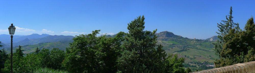 Eine Foto von Verucchio aus ins Hinterland. Zu sehen ist eine Hüfthohe Steinmauer, dahinter erstreckt sich eine Bergige Region, die ganz grün ist. Die Berge sind bewaldet oder Aber Felder Erstrecken sich. Der Himmel ist strahlend blau