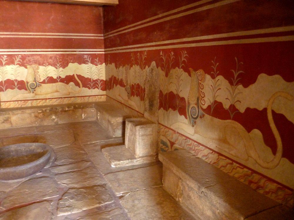 Der Alabasterthron zwischen den Bäken. Dahinter eine Rotweiß bemalte Wand, links und rechts des Thrones sind zwei Graifen die zum Thron hinsehen.