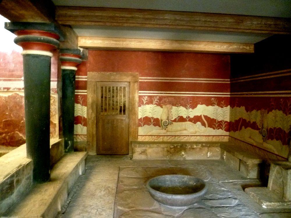 Ein Raum mit Rot weis bemalten Wänden. Links felht eine wand, dort stehen aber Blaue Säulen - vor diesen steht eine nidrige Steinbank. Diese zeiht sich auch an den anderen Wänden endlang- in der Mitte des Raumes steht eine steinenernde Schale.