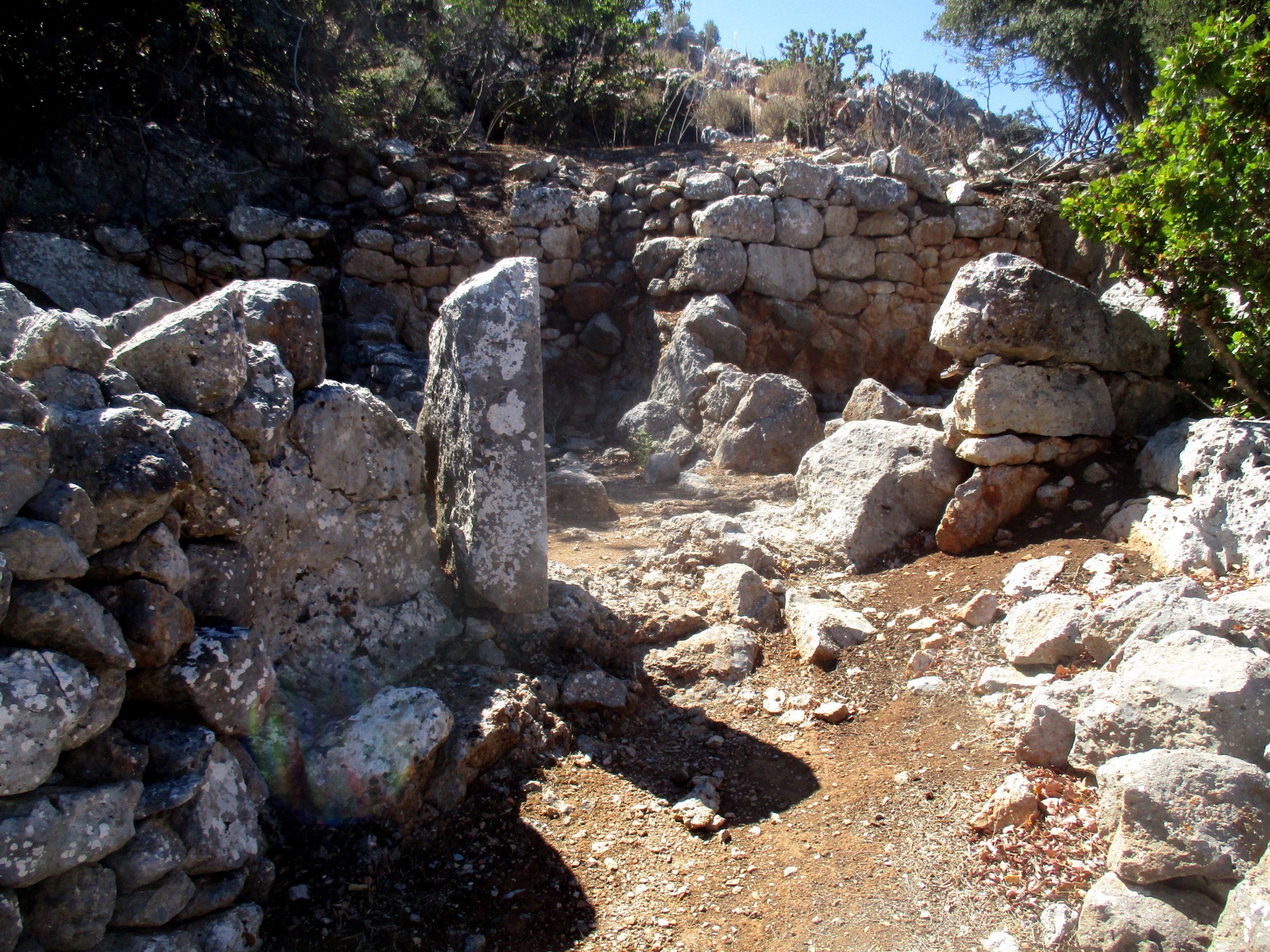Die Ruiene eines Hauses das aus grauem Stein gemauert war. Sie ist etwa hüfthoch erhalten.
