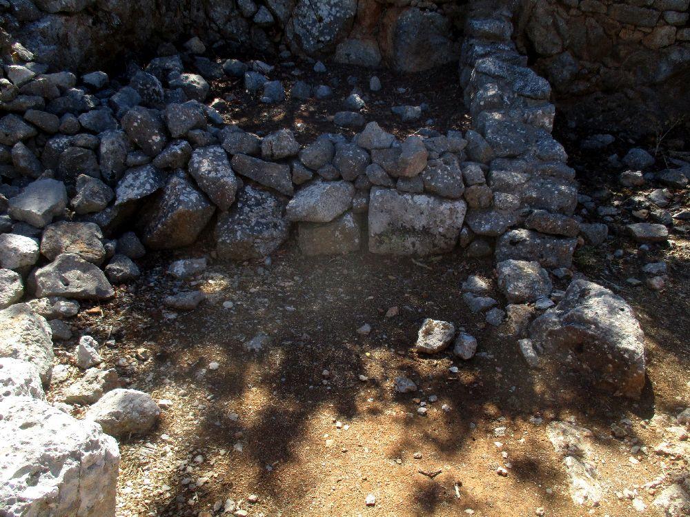 Ein Raum aus grauen Stein gemauert auf gelben Sand. Es scheint eine gemeuerte empore oder einen Altar gegeben zu haben.