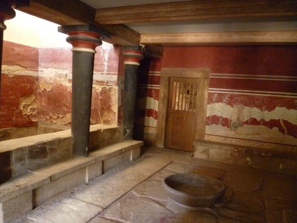Ein Rot angemalter halboffener Raum. Auf einer seite befinden sich böaue Säulen. hinter diesen liegt ein Bad. an der Ballustrade befinden sich niedrige sitzbänke aus grauem Stein.