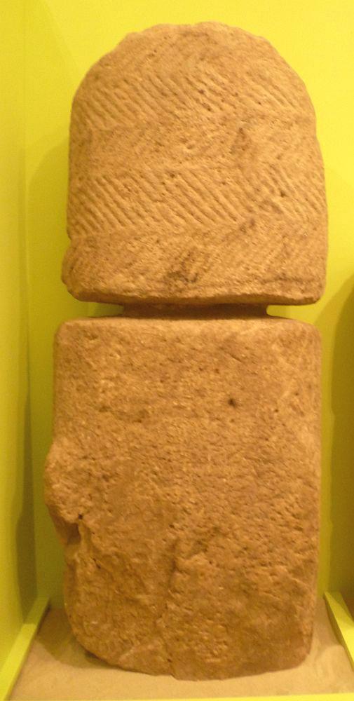 Eine aus zwei teilen zusammengesetzte Sandsteinstele. Der Stein ist leicht rötlich. Die Stle ist oben abgerundet. sie ist mit einem Muster aus dünnen linien verziehrt.