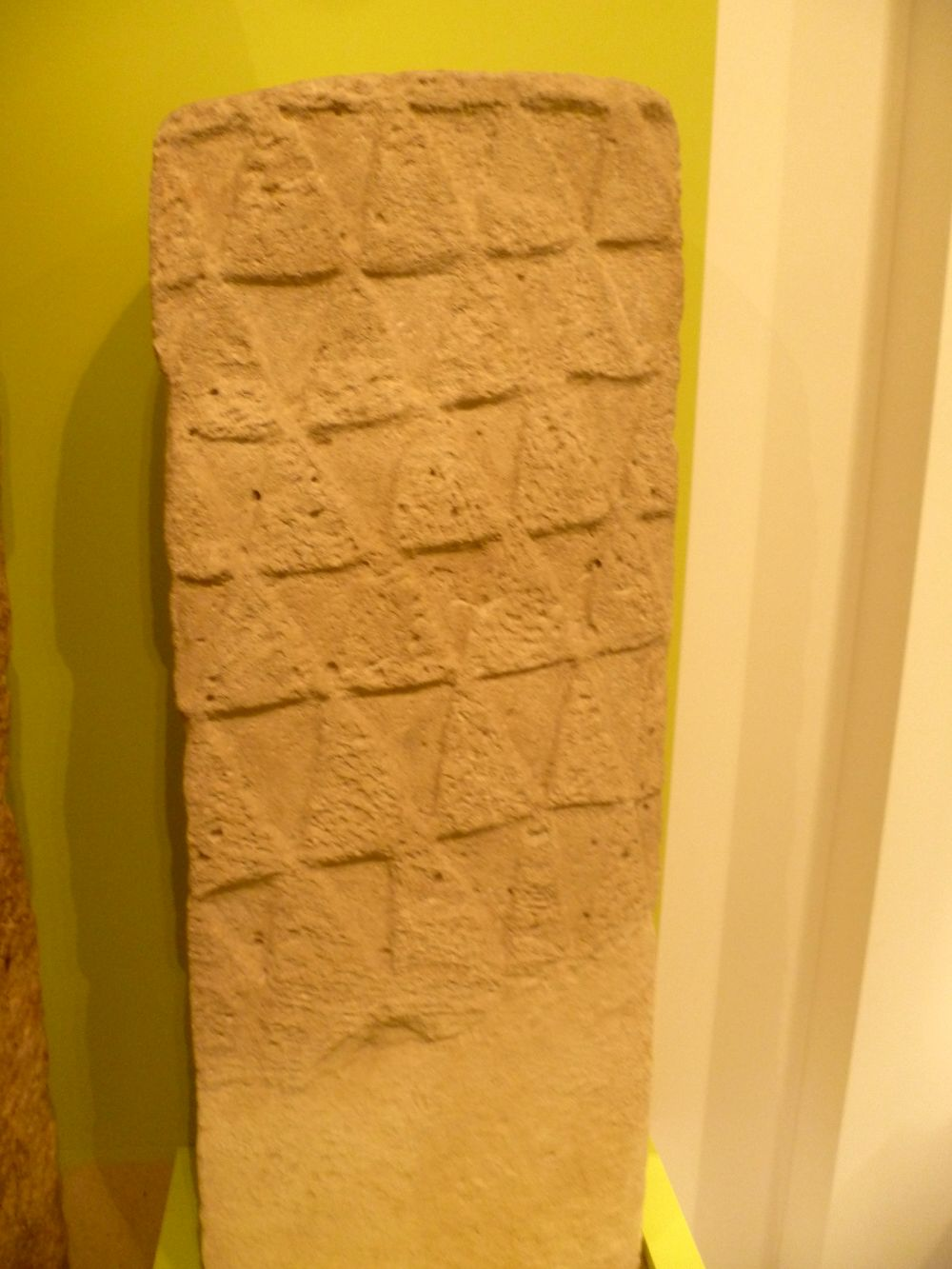 Eine Steinstele aus leicht rötlichem Sandstein. Sie ist mit einem Relief aus Dreiecken verzeiht