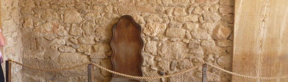 Der Holzthron steht vor einer Wand aus groben stein.