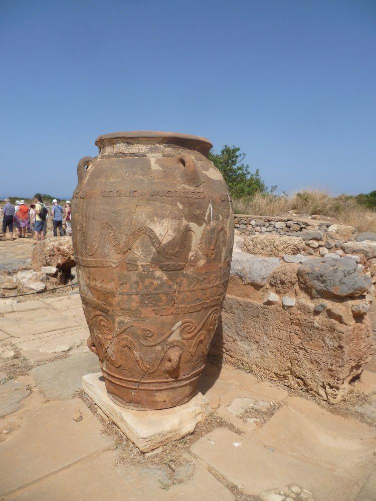 Ein Großer Phitao, das ist ein reich verziehrtes ca 2m hohes Keramikgefäß, zwischen Ruinen aus rotem Stein.