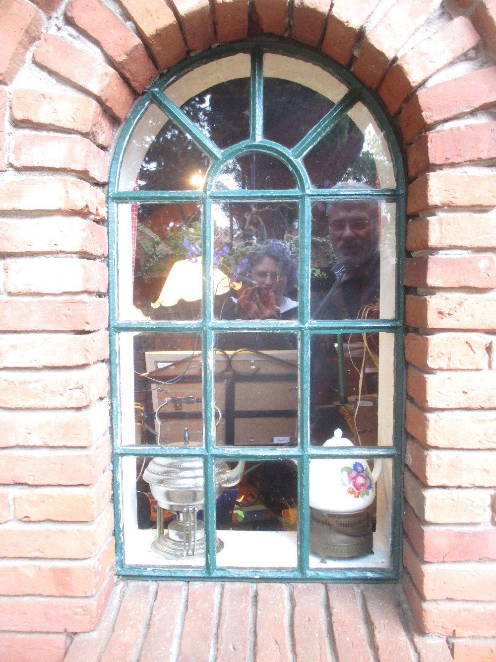 Das Spiegelbild von einer Jungen Frau und einem Alten Mann in einem Fenster.
