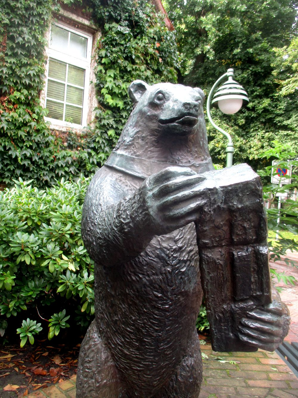 Der Esener Bär. Eine Bronzeskulptur eines Bären mit einem Großen Ziegelstein in der Hand.