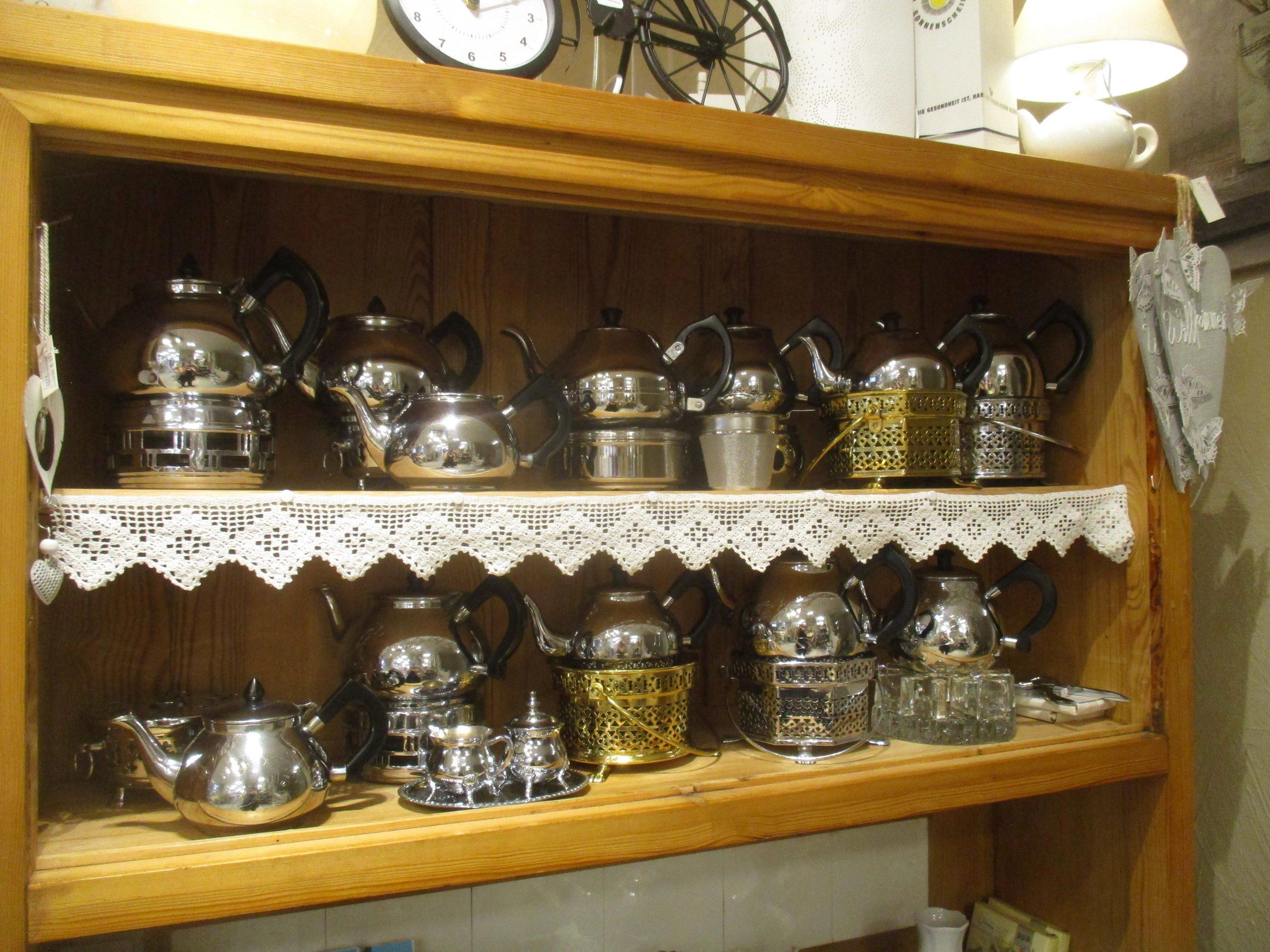 Ein Holzregal mit vielen Bauchiegen Metallkannen.