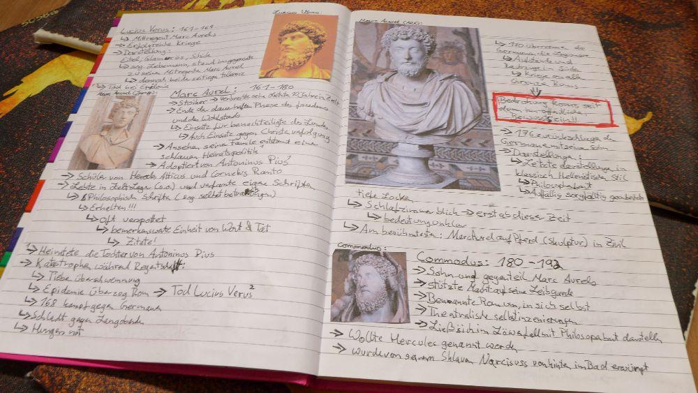 Ein aufgeschlagenes Notizbuch in dem Viele Bilder von römischen Kaisern eingeklebt sind mit Text dazu